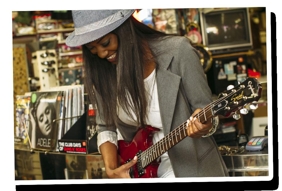 Une musicienne qui fait de la guitare mais aussi de la basse et du piano est en train de jouer. Elle apprend le rythme de ses morceaux préférés en rigolant et en souriant. Elle tient une magnifique guitare et joue avec ses doigts. Elle essaie d'avoir le rythme.